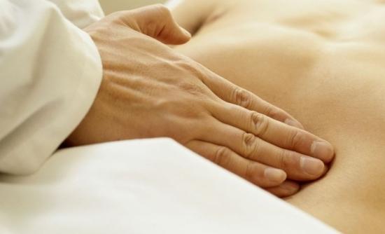 Врач, пальпируя живот пациента, выявляет наличие пупочной грыжи