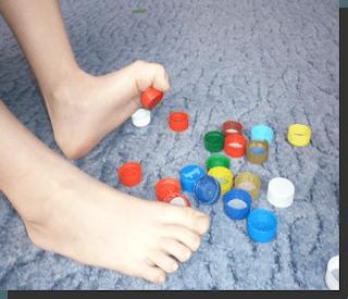 Ребенок собираем пальцами ног мелкие предметы